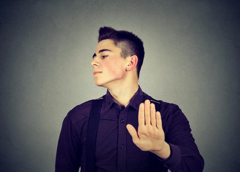 Angry man giving talk to hand gesture with palm outward. Closeup portrait angry man giving talk to hand gesture with palm outward on gray wall background stock image