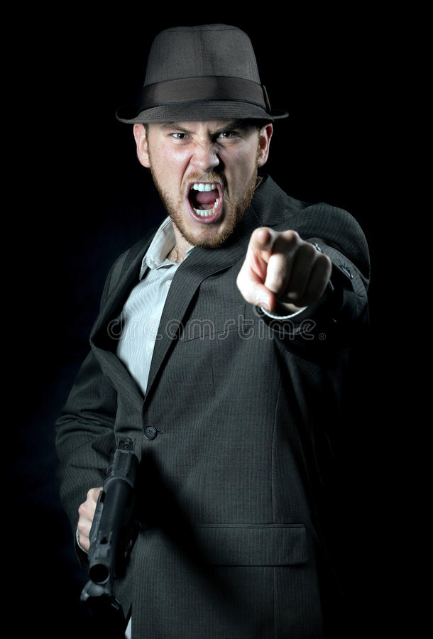 Angry Man with Gun. An angry man with a gun pointing at you royalty free stock images