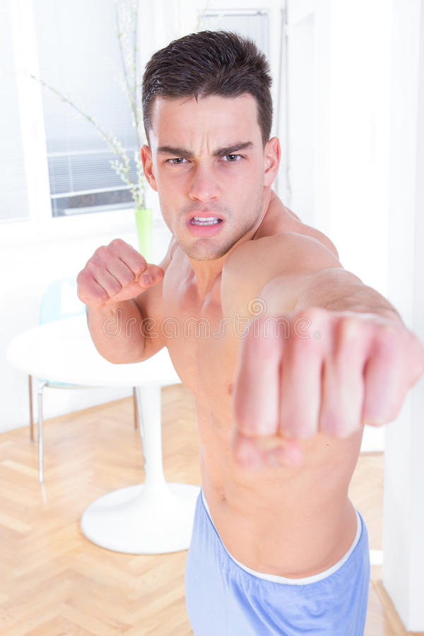 Angry man hitting into camera with clenched fist royalty free stock images