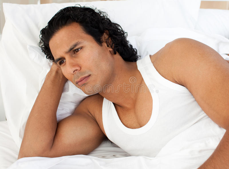 Angry man lying in the bed royalty free stock photo