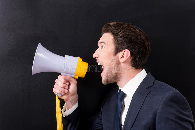 Angry man is making noise through megaphone. Hostile announcement concept. Antagonistic young manager is screaming through bullhorn and expressing aggression stock photos