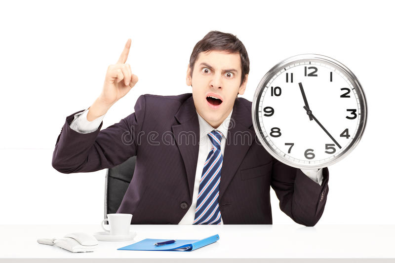 Angry man in an office, holding a clock and pointing