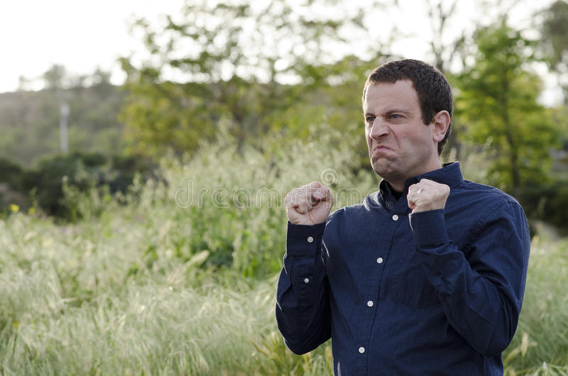 Angry man outdoors with clenched fists. stock photos
