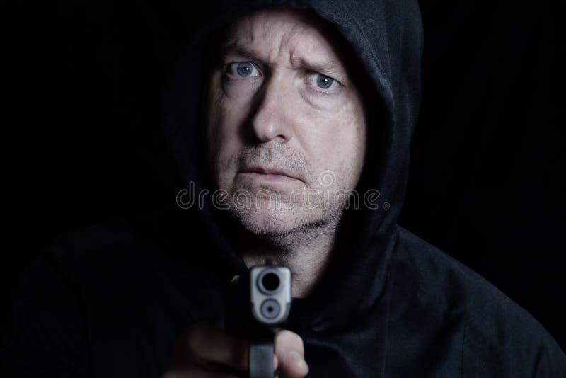 Angry man pointing gun forward stock photography