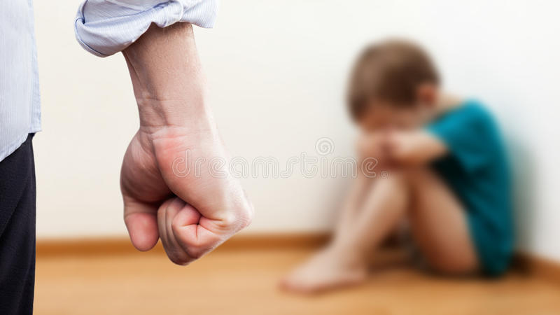 Angry man raised fist over wall corner sitting child boy royalty free stock photography