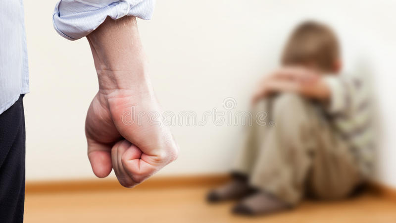 Angry man raised fist over wall corner sitting child boy stock photography