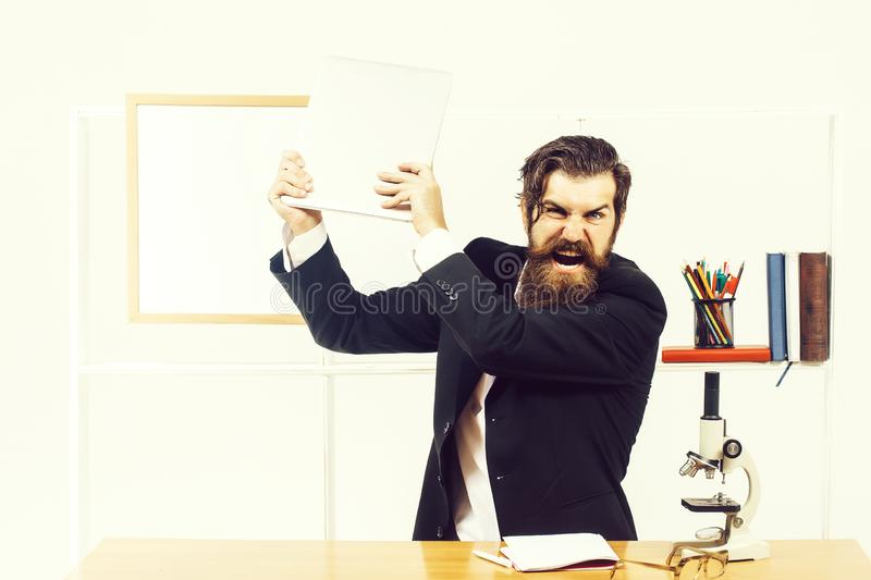Angry man smashes laptop. Angry man businessman male scientist hipster smashes laptop furiously in office with board for copy space on white background stock photo