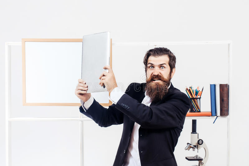 Angry man smashes laptop. Angry man businessman male scientist hipster smashes laptop furiously in office with board for copy space on white background stock photos