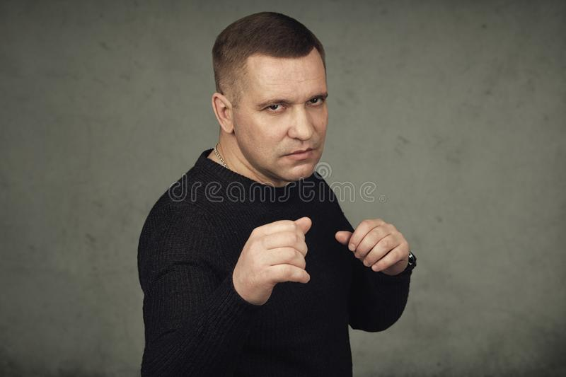Angry man standing in a fighting position. Over grey wall stock photos