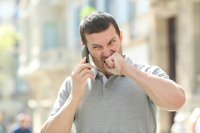 Angry man talking on phone having problems in the street. Angry man talking on mobile phone having problems standing in the street royalty free stock photo