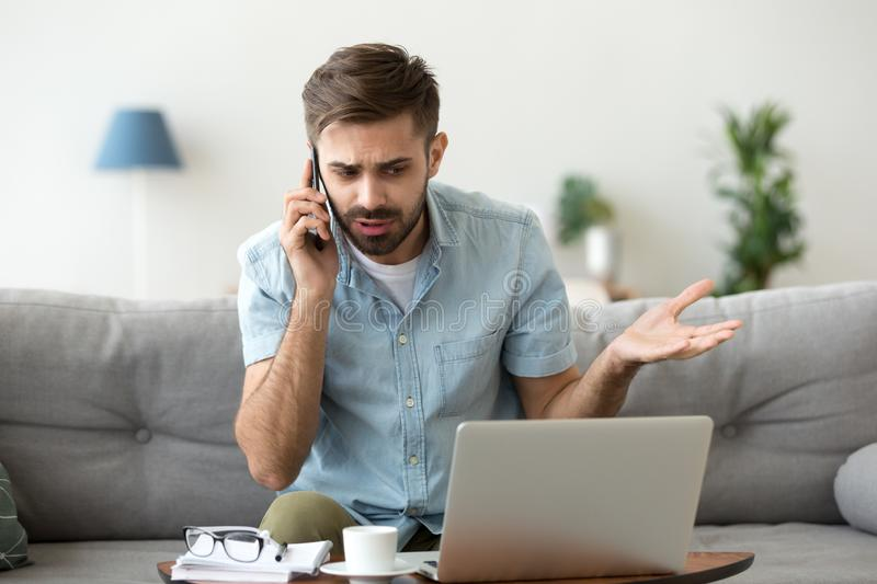 Angry man talking on phone disputing over computer laptop problem stock photography