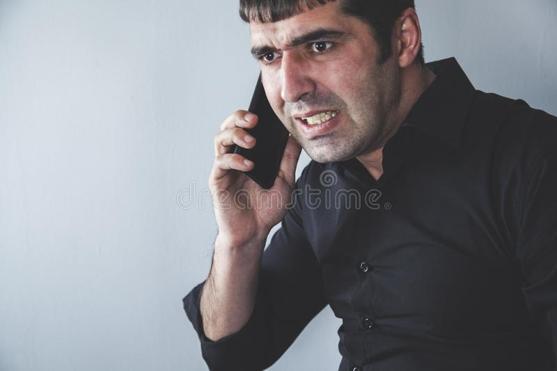 Angry man talking in phone stock photography