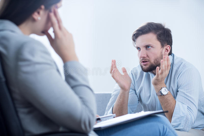 Angry man talking with psychiatrist. Angry men talking with psychiatrist or psychologist stock photography