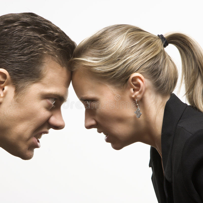 Angry man and woman. Caucasian mid-adult man and woman with foreheads together staring at each other with hostile expressions