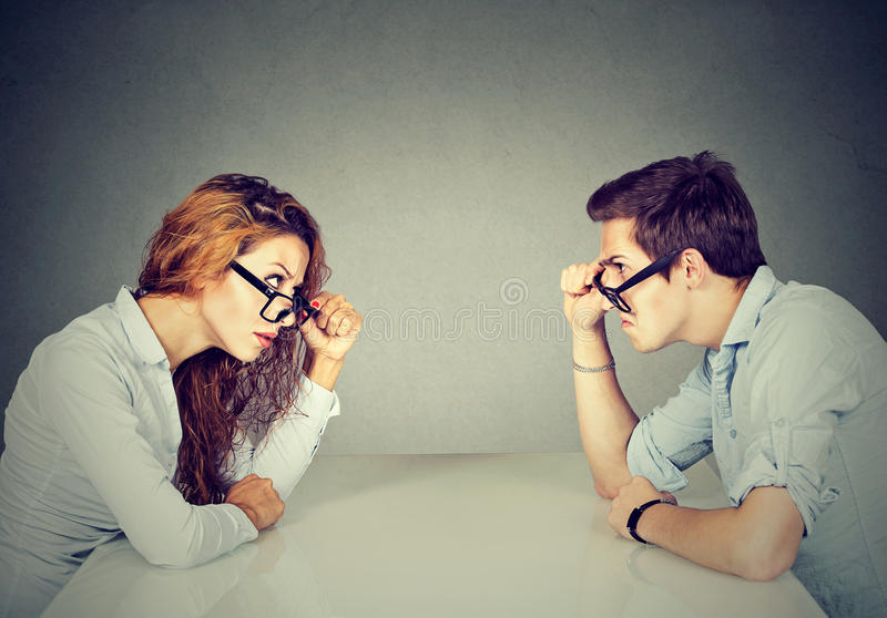 Angry man and woman sitting at table looking at each other with hatred and disgust royalty free stock photos