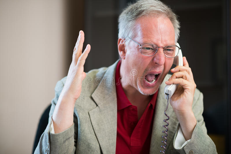 Angry man yelling on the phone. Portrait of an angry man yelling on the phone royalty free stock photos