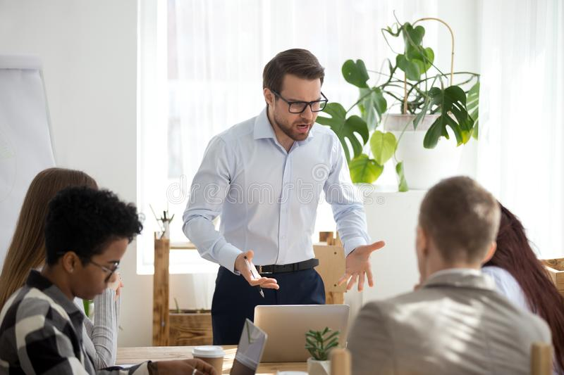 Angry manager boss shouting at group office meeting scolding employees royalty free stock images