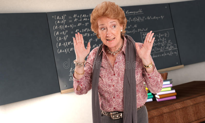 Angry Maths Teacher. Maths teacher with an impatient gesture in and empty classroom royalty free stock image