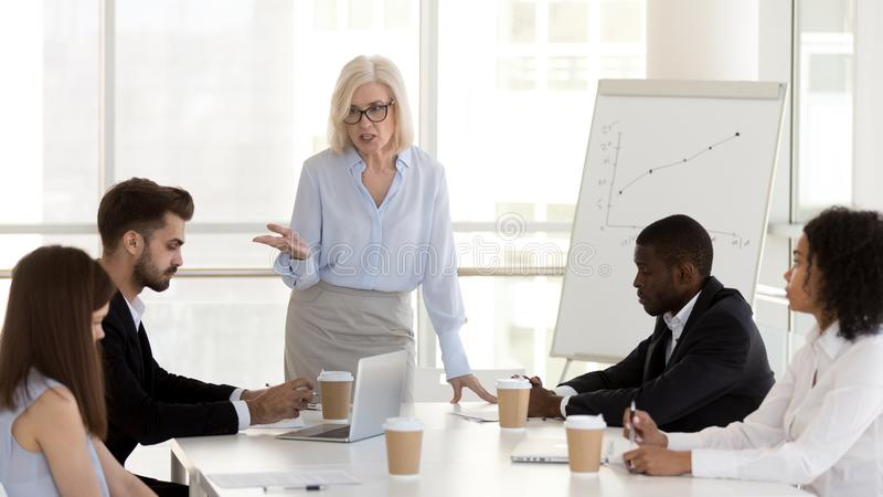 Angry mature businesswoman, boss scold employees for bad work results stock photos