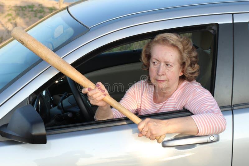 Angry mature female driver holding baseball bat stock photo