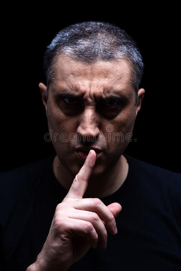 Angry mature man with an aggressive look making the silence sign in a threatening and creepy way. stock photo