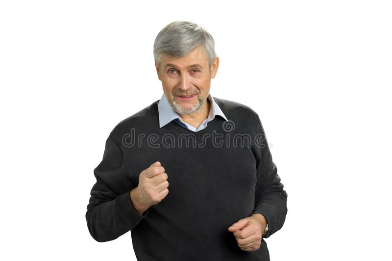Angry mature man on white background. Portrait of senior man showing fist. Irritated mature man putting his fist up. Facial expressions, emotions and stock image