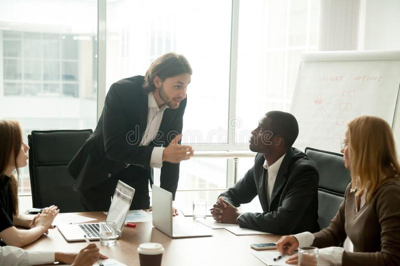 Angry mean boss scolding employee for bad work at meeting stock images