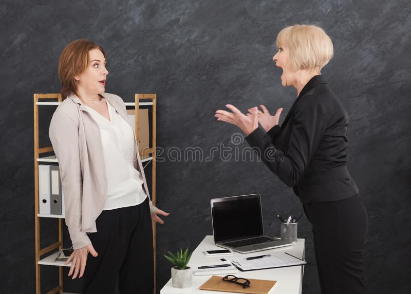 Angry middle aged boss yelling at young employee royalty free stock images