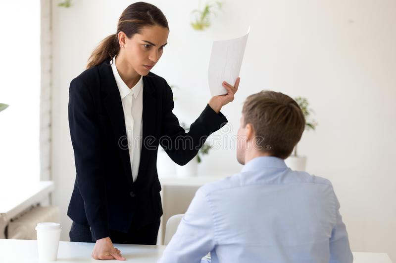 Angry boss scolding unqualified employee telling about mistake in report royalty free stock image
