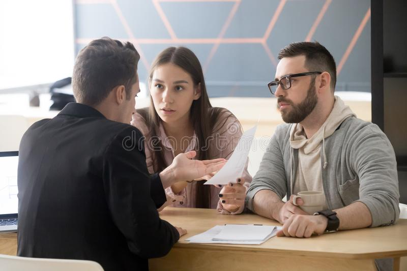 Angry millennial couple complaining about bad contract disputing stock image