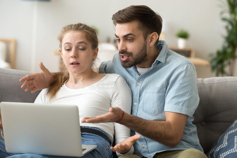 Angry millennial couple having computer problems at home stock photography