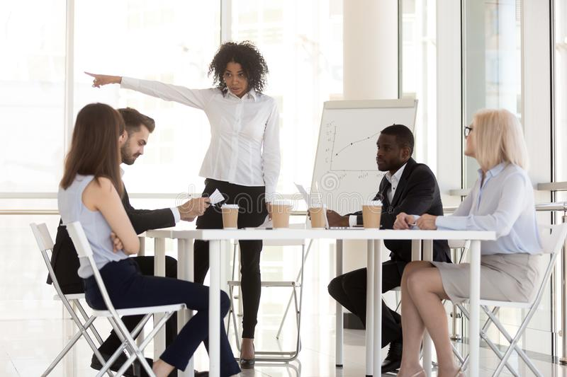 Angry mixed-race manager firing incompetent employee asking to l royalty free stock photography