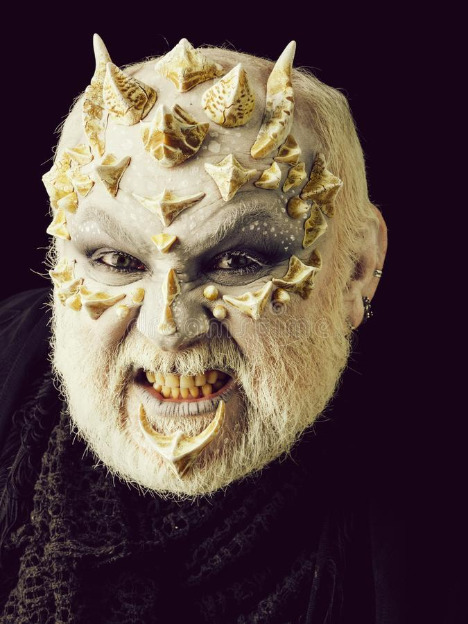 Angry monster man baring teeth. With white eyes and bearded thorny face on black background. Horror and fantasy concept stock photos