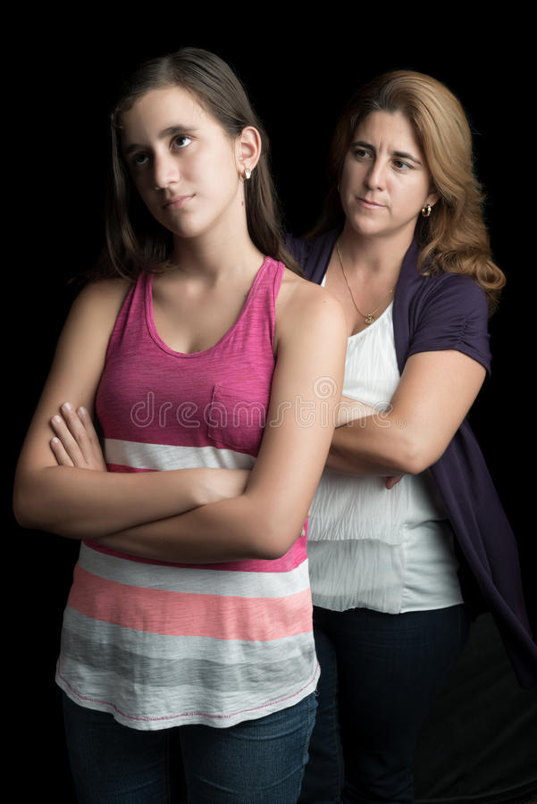 Angry mother with her teen daughter ignoring her. Angry mother with her teenage daughter ignoring her isolated on black stock photos