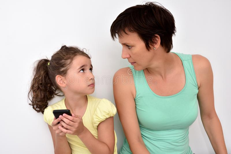 Angry mother and scared daughter with smartphone looking at each other royalty free stock photo