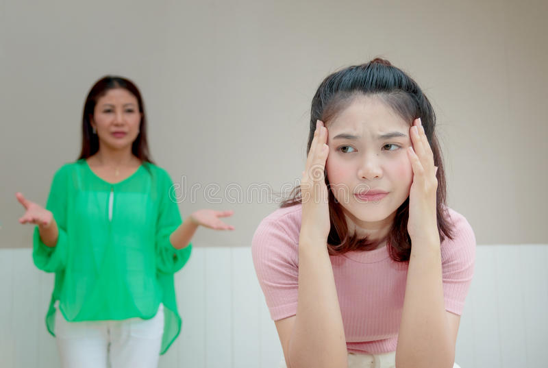 Angry mother stands behind her daughter complain something stock photos