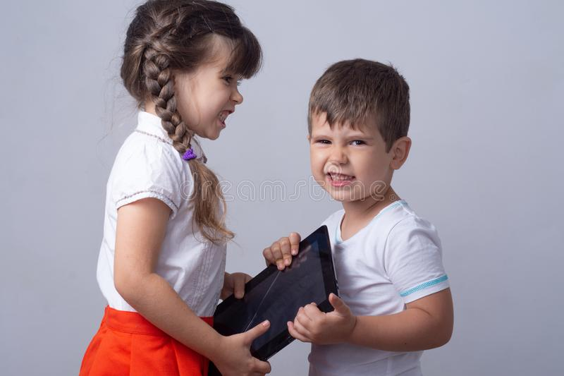 Angry and nervous kids scolding with each other. Family and modern technology addiction concept. Gadgets overuse concept. Internet royalty free stock images