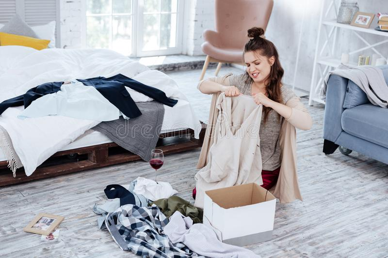 Angry nervous woman tearing clothes of husband after treason. Nervous woman. Angry nervous woman feeling hysterical while tearing clothes of husband after stock photos