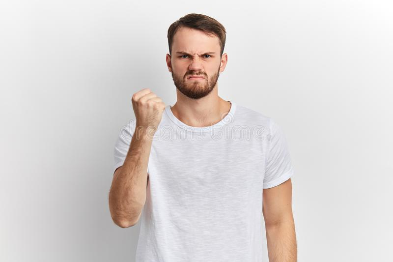 Angry nervous young man shows clenched fist, giving warning stock photos