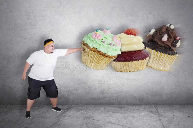 Angry obese man punching cupcakes. Picture of an obese man refusing to eat sweet food by punching cupcakes in the studio with angry expression stock photos