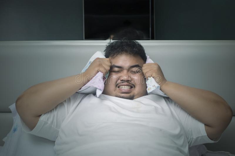 Angry obese man unable to sleep. Sleeping disorder concept: Angry obese man unable to sleep during closing his ears with a pillow stock images