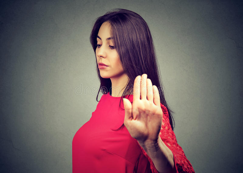Angry offended young woman giving talk to hand gesture stock photo