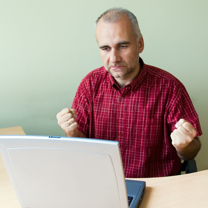 Angry office worker. Working on laptop with hope royalty free stock image