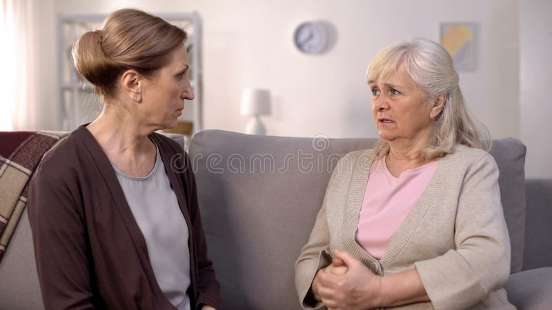 Angry old women looking each other sitting in living room, communication problem stock images