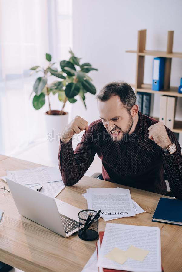 angry and overworked businessman at workplace with laptop stock photos