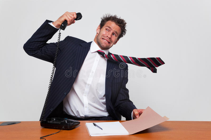 Angry phone call. Businessman getting a phone call from an angry person shouting down the line royalty free stock image