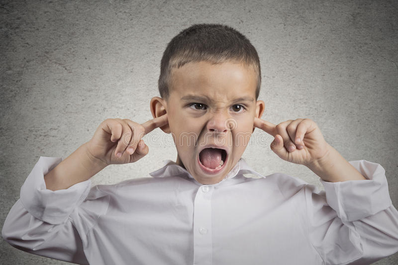 Angry off boy plugs his ears with fingers. Closeup portrait angry annoyed off boy plugs his ears with fingers sticking out tongue looking with funny negative stock photography