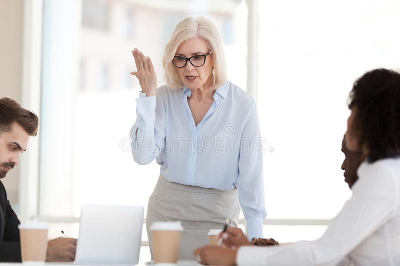 Angry powerful mature boss scolding employees at group corporate royalty free stock photo