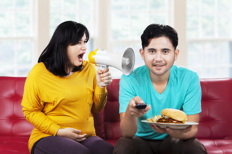 Angry pregnant woman at her husband. Portrait of angry pregnant women at her husband in the home royalty free stock image
