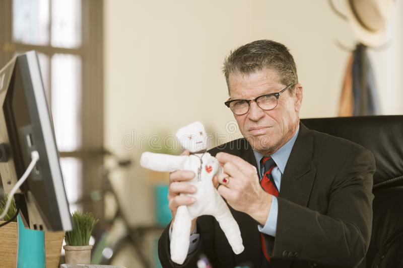 Angry Professional Man Jabbing a Voodoo Doll. Angry professional man putting a pin into the heart of a Voodoo doll stock images
